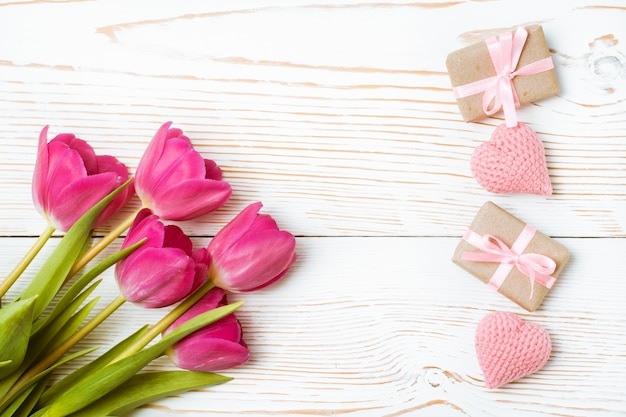 Boeket tulpen, verpakte geschenken en gebreide harten op een wit hout, bovenaanzicht