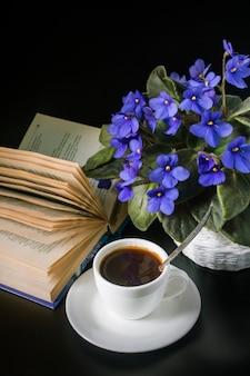 Boeket van afrikaanse viooltjes met een kopje koffie en een open boek op een zwarte ondergrond.