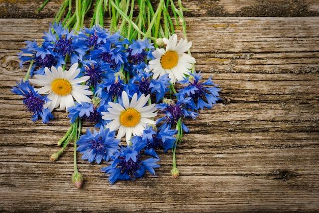 Boeket van blauwe korenbloemen en madeliefjes close-up op een houten