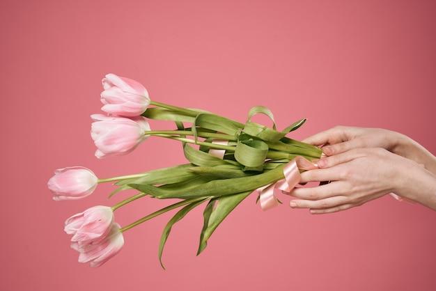Boeket van bloemen in de dag van de de giftwens van handen roze achtergrond