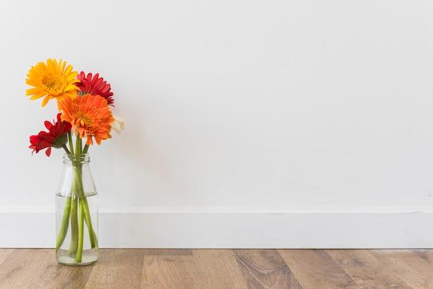 Boeket van bloemen in vaas dichtbij muur