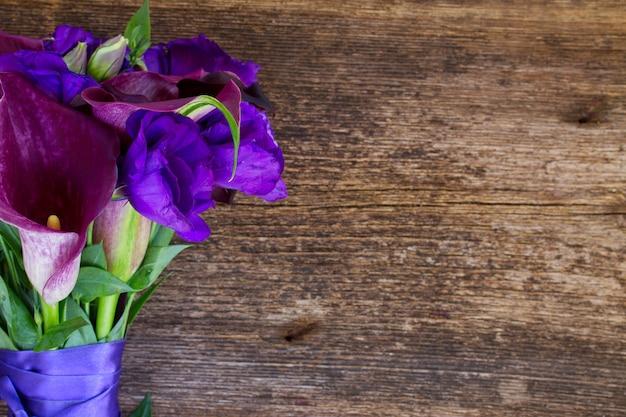 Boeket van calla lelie en eustoma bloemen op houten tafel