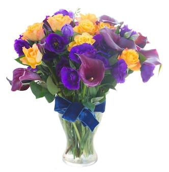 Boeket van calla lelie, rozen en eustoma bloemen in glazen vaas op wit wordt geïsoleerd