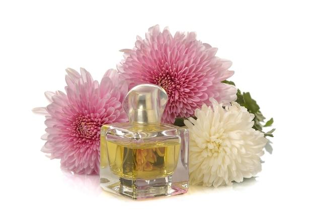 Boeket van chrysanten en een fles parfum op een witte geïsoleerde achtergrond. herfst bloemen