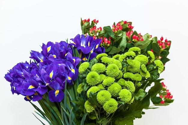 Boeket van chrysanten en irissen op een witte achtergrond. kleurrijk bloemenboeket witte achtergrond