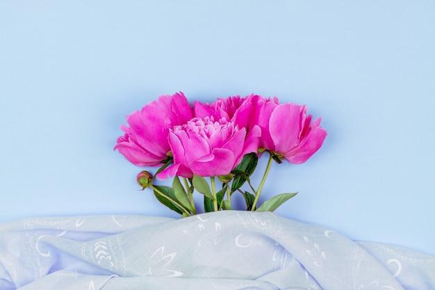 Boeket van donker roze pioen bloemen close-up en roze stof op blauwe achtergrond bovenaanzicht