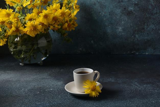 Boeket van doronicum bloemen en kopje koffie. zomer concept