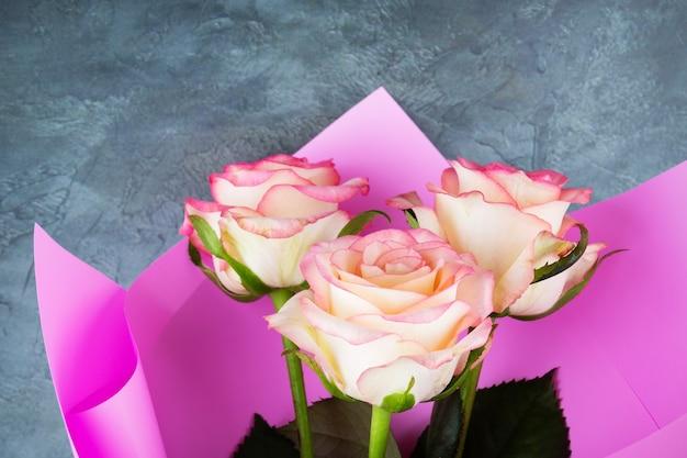 Boeket van drie rozen in roze wrapper close-up op grijze achtergrond