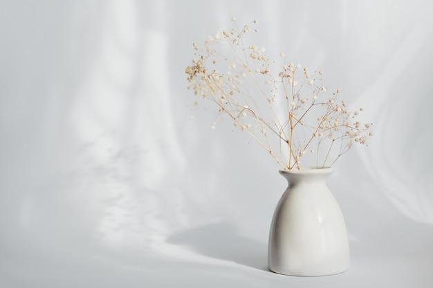 Boeket van droge gypsophila bloemen in een witte vaas op lichte muur