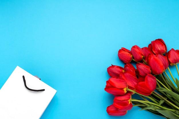 Boeket van fel rode tulpen in een witte geschenk tas op een blauwe achtergrond. conceptie van gefeliciteerd en een geschenk. plat lag, bovenaanzicht