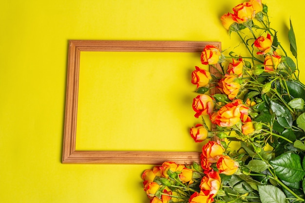 Boeket van feloranje rozen met houten frame op felgele achtergrond