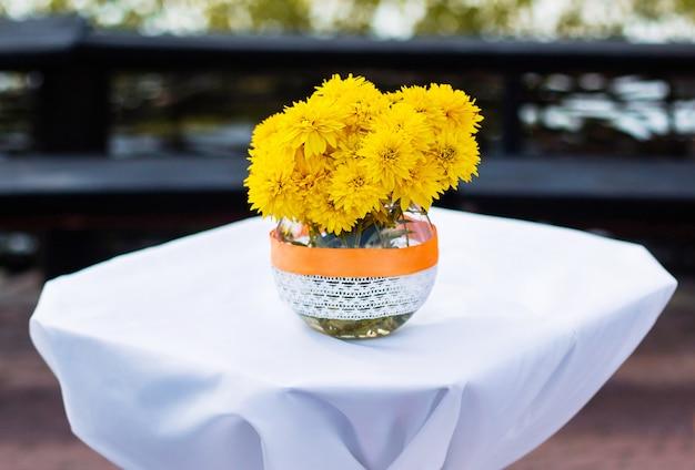 Boeket van geeloranje bloemen staat in een kruik op de tafel, bruiloft bloemen, huwelijksceremonie, bruiloft decoraties