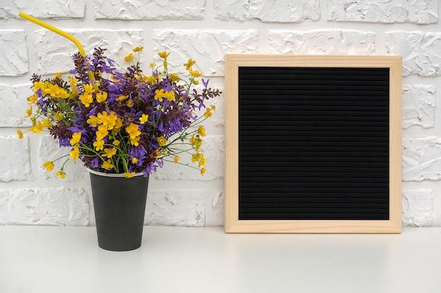 Boeket van gekleurde bloemen in zwart papier koffiekopje met cocktailstro en lege zwarte letter boord op tafel
