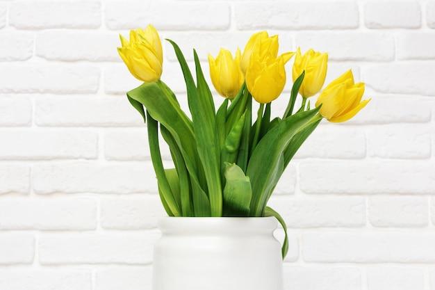 Boeket van gele bloemen tulp in kleine keramische vaas natuurlijke lentebloemen in de kamer.