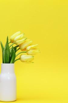 Boeket van gele bloemen tulp in kleine keramische vaas op gele achtergrond. natuurlijke lentebloemen.