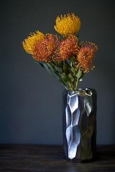 Boeket van gele en oranje exotische protea bloemen in een metalen vaas op een donkere achtergrond