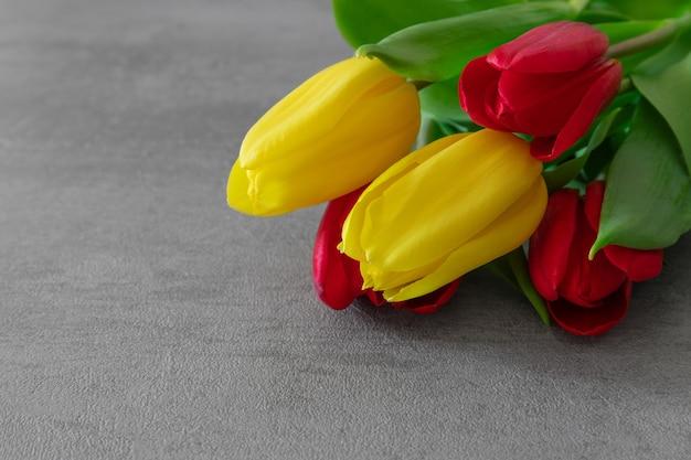 Boeket van gele en rode tulpen op grijs cement
