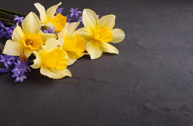 Boeket van gele narcissen en lilac bloemen op een zwarte achtergrond, exemplaarruimte