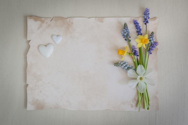 Boeket van gele narcissen en muscaribloemen op een houten achtergrond met harten.
