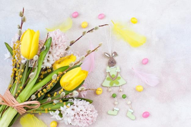 Boeket van gele tulpen en roze hyacinten, wilg en mimosa, konijn, eieren en veren