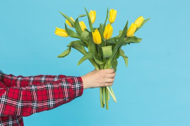 Boeket van gele tulpen in de hand van vrouwen op blauwe achtergrond.
