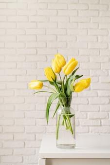 Boeket van gele tulpen in een glazen vaas op een witte bakstenen muur achtergrond