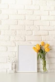 Boeket van gele tulpen in een glazen vaas, witte kaars en leeg fotolijstje op een witte bakstenen muur achtergrond. mock-up ontwerp