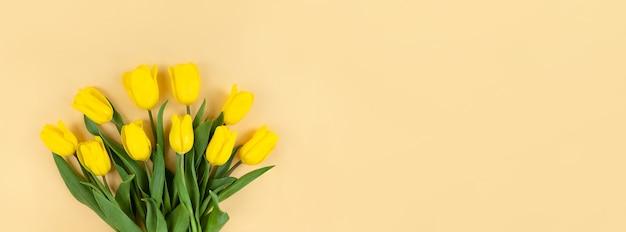 Boeket van gele tulpen op een beige achtergrond met kopie ruimte.
