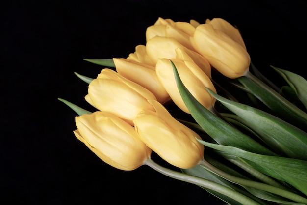 Boeket van gele tulpen op een zwarte achtergrond.