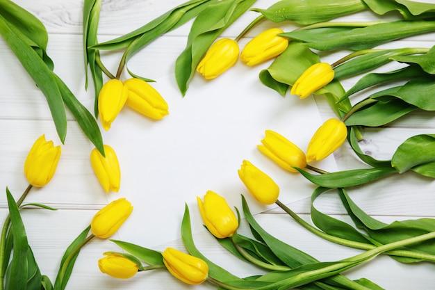 Boeket van gele tulpen op houten achtergrond.