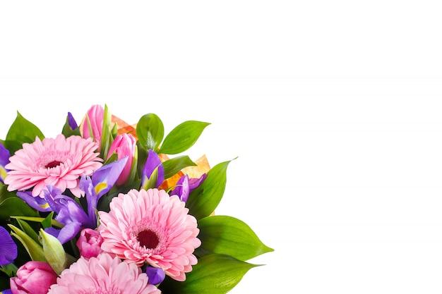 Boeket van gerbera's, irissen en tulpen op een witte muur
