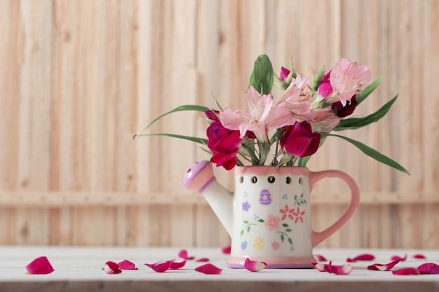Boeket van heldere bloemen in gieter op houten achtergrond