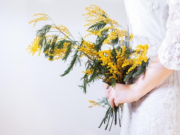 Boeket van heldere, gele bloemen in de handen van een jonge vrouw in een witte jurk. afgelegen, close-up.