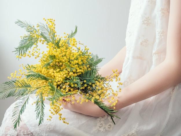 Boeket van heldere, gele bloemen in de handen van een jonge vrouw in een witte jurk