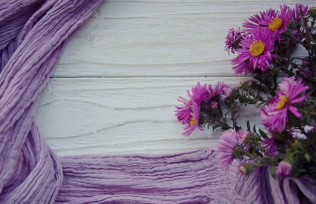 Boeket van heldere herfstbloemen en een paarse sjaal die een frame vormt
