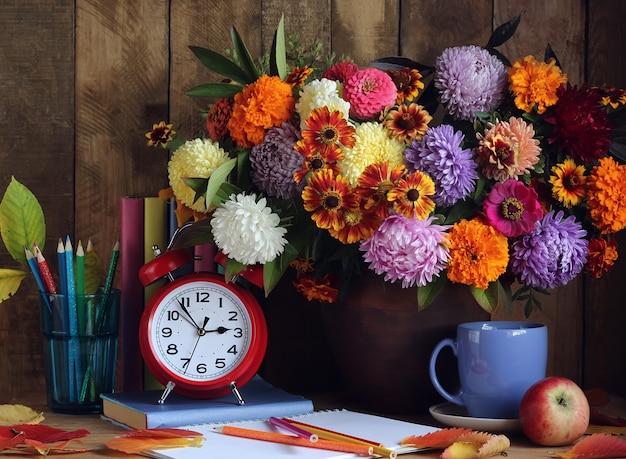 Boeket van herfst bloemen, een stapel boeken, herfstbladeren en rode wekker op de tafel.