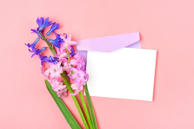 Boeket van hyacinten bloemen, lila envelop en witte notitie papier op roze tafel