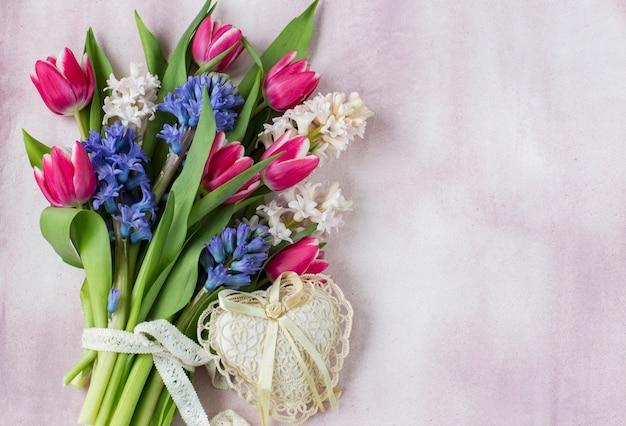Boeket van hyacinten en tulpen en een hart van kant op een roze achtergrond