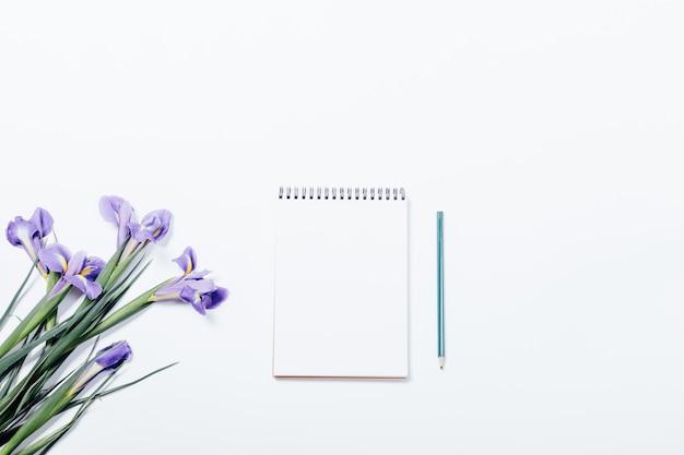 Boeket van irissen en notitieboekje met potlood op een witte tafel