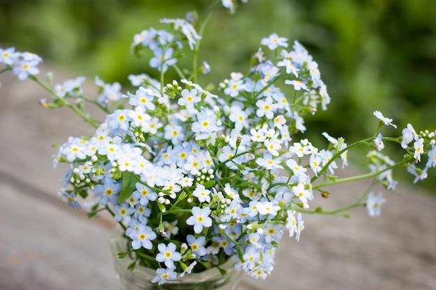 Boeket van kleine blauwe wilde bloemen in een vaas, bovenaanzicht
