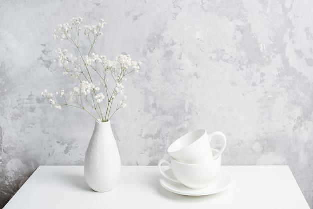 Boeket van kleine delicate bloemen gypsophila in vaas en en twee witte kopjes voor thee of koffie op tafel