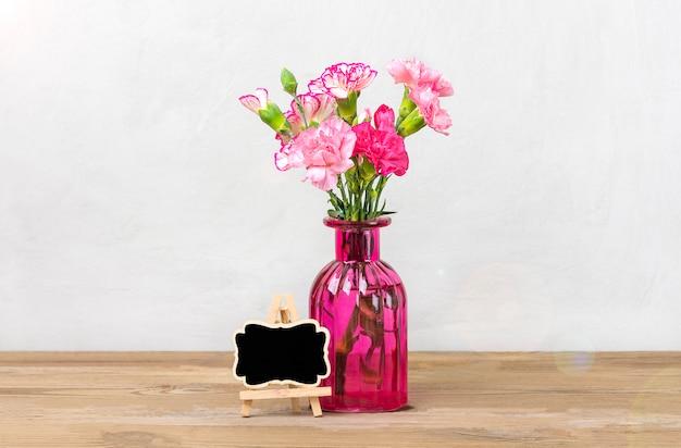 Boeket van kleine gekleurde roze anjers in vaas, frame op houten achtergrond en grijze muur