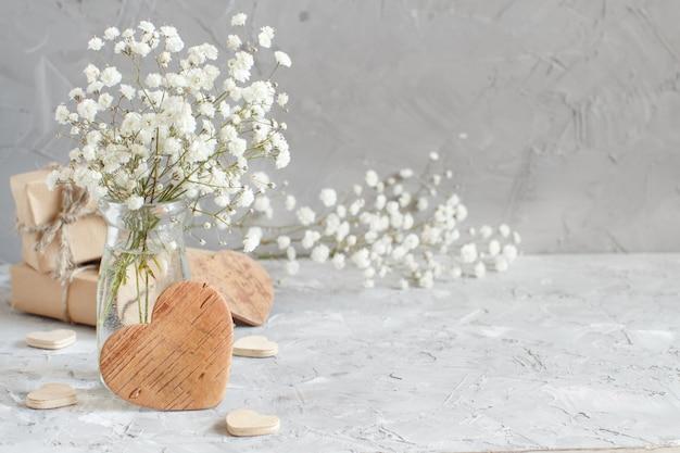 Boeket van kleine witte bloemen en houten hartjes op een grijze achtergrond