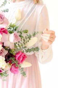 Boeket van kleurrijke bloemen in de hand van de vrouw