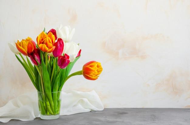 Boeket van kleurrijke natuurlijke tulpen in een glazen vaas met water op een betonnen achtergrond.
