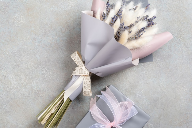 Boeket van lavendel en lagurus met grijs-paarse verpakking met een geschenkdoos in een enkele kleur.