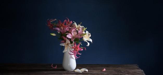 Boeket van leliebloemen in vaas op donkere achtergrond