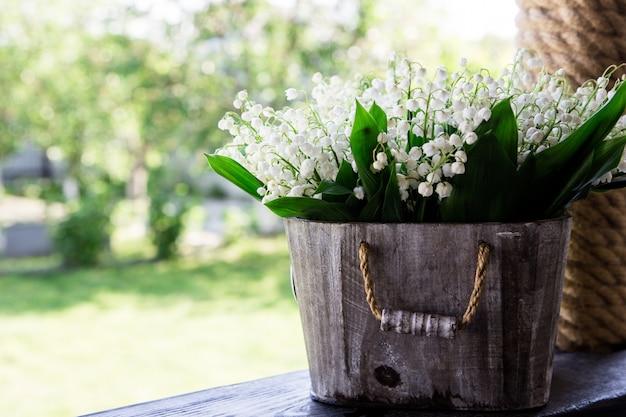 Boeket van lelietje-van-dalen in een mand. florale achtergrond met plaatsen voor uw tekst