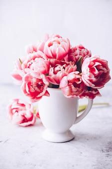 Boeket van lente tulpen in vaas op shabby chic achtergrond