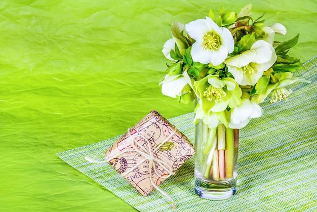 Boeket van lentebloemen en geschenkdoos op groene tafel